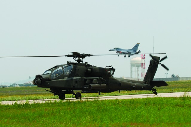 An AH-64 Longbow Apache helicopter taxis the runway as a F-16 Fighter jet takes off during a joint Army, Air Force exercise July 7, 2013.