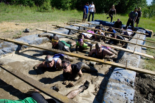 Mudders crawl through the mudpit at the 2nd annual Arctic Tough Mudders Mud Run July 13.