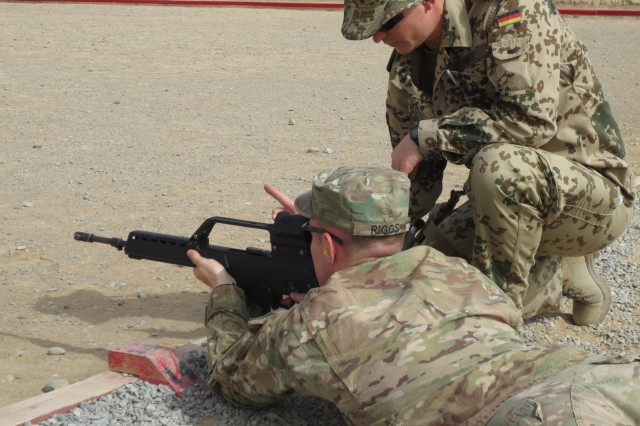 A German army soldier with the 1st NATO Signal Battalion coaches 1st Lt. Matthew Riggs as he fires a Heckler & Koch G36 assault rifle, July 11, 2013, at Kandahar Airfield, Afghanistan. Riggs, a postal officer, and 13 other Soldiers assigned to the Headquarters and Headquarters Company, 3rd Sustainment Brigade, received the rare opportunity to earn the German Armed Forces Badge of Marksmanship, or Schützenschnur, while deployed in support of Operation Enduring Freedom.