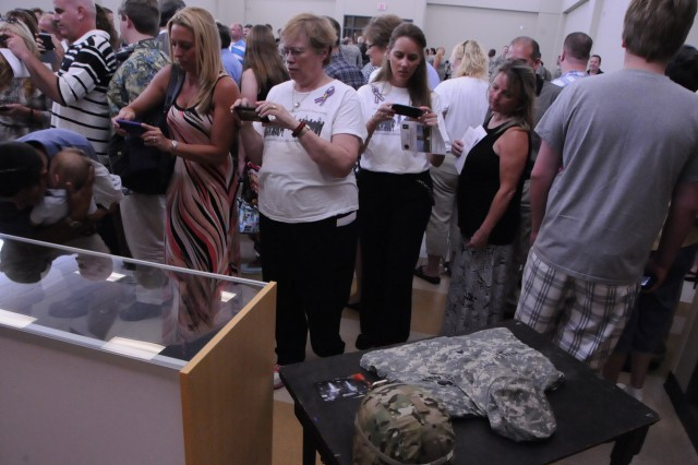 Friends, family, Soldiers and supporters take pictures of the memorabilia after the memorialization ceremony for the Sgt. Thomas J. (T.J.) Butler IV Armed Forces Reserve Center on July 13 in Wilmington, N.C. Sgt. Butler was killed in Khost City, Afghanistan on October 1, 2012.