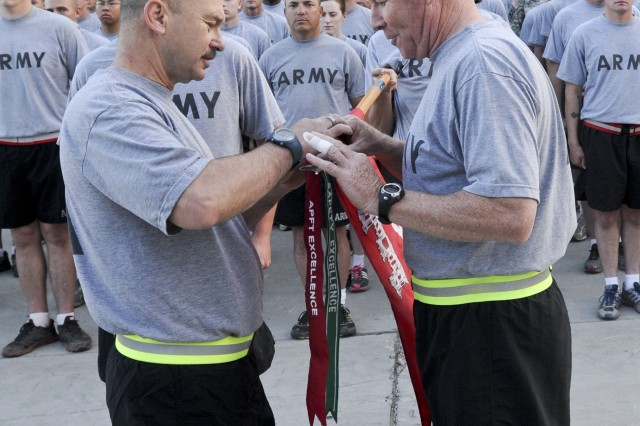 FORT CARSON, Colo. -- Sgt. Maj. Richard Joyce, acting senior enlisted advisor, 4th Infantry Division and Fort Carson, and Brig. Gen. Michael Bills, acting senior commander, 4th Inf. Div. and Fort Carson, pin on an Army physical fitness test excellence streamer to the 544th Engineer Company, 52nd Engineer Battalion, guidon, July 19, 2013. The APFT Excellence streamer was awarded for the 544th Eng. exceeding the CG's APFT standard of a company average of 250 points, with an 85 percent participation rate. They scored an average of 279 with 87 percent participation, May 29.