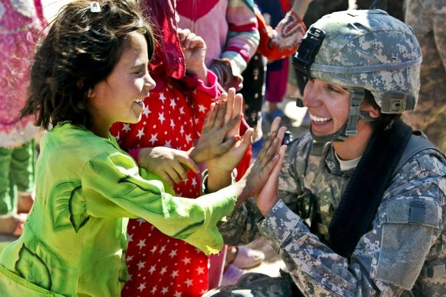 "Sgt. Stephanie Tremmel, with the 86th Special Troops Battalion, 86th Infantry Brigade Combat Team, interacts with an Afghan child while visiting the village of Durani. Having females as part of combat teams can be a ""force multiplier,"" since women can engage with the local women in a particular country. Last month the Army announced its plan to integrate women into combat roles, opening positions within 27 brigade combat teams, which include nine National Guard brigade combat teams."