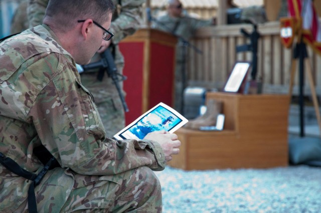 "A U.S. Soldier reads a program pamphlet prior to a memorial ceremony held for Spc. Hilda I. Clayton at Forward Operating Base Gamberi in Laghman province, Afghanistan, July 8, 2013. Clayton, of Augusta, Ga., was forward-deployed as the combat camera asset covering the 4th Brigade Combat Team, 1st Cavalry Division, ""Task Force Long Knife,"" at the time of her death. She died while photographing Afghan National Army soldiers conduct a live-fire training exercise when a mortar system failed and exploded, July 2. Clayton served as a combat documentation/production specialist assigned to the 55th Signal Company (Combat Camera), 21st Signal Brigade, based at Fort Meade, Md.  (U.S. Army photo by Sgt. Richard W. Jones, Jr./Released)"