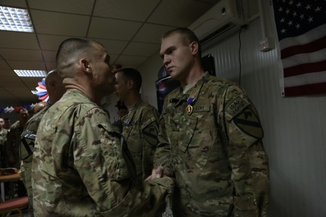 "U.S. Army Col. William Benson, commander of the 4th Brigade Combat Team, 1st Cavalry Division, congratulates Spc. James Young, a food service specialist assigned to the 2nd Battalion, 7th Cavalry Regiment, 4th BCT, 1st Cav., Div., after presenting him the Purple Heart medal at Forward Operating Base Naghlu High, Kapisa province, Afghanistan. The ""Long Knife"" Brigade, 4th BCT, 1st Cav., Div., based out of Fort Hood, Texas, has been deployed to eastern Afghanistan for the last nine months. (U.S. Army photo by Staff Sgt. Richard Andrade/Released)"
