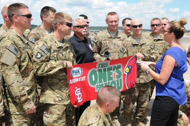 """Al Hrabosky, aka """"The Mad Hungarian,"""" center, a former Major League baseball pitcher from 1970-1982, and a colorful television broadcaster for the St. Louis Cardinals since 1985, prepares to do a group """"Shout Out"""" with Soldiers of the Missouri National Guard's 1st Battalion, 135th Attack Reconnaissance Battalion, while Colleen Lotz, right, feature producer for FoxSports Midwest, directs the group. Hrabosky was at Fort Hood, Texas' Robert Gray Army Airfield July 18 taking part in """"Shout Outs"""" that will air during a telecast of the July 25, 2013 standoff between the St. Louis Cardinals and the Philadelphia Phillies. The 1-135 ARB will deploy more than 300 Soldiers as an attack and reconnaissance asset to Afghanistan after completing pre-deployment training at Fort Hood, Texas with First Army Division West's 1st Battalion, 291st Aviation Regiment, 166th Aviation Brigade. (Photo by Michael M. Novogradac, Division West Public Affairs)"""