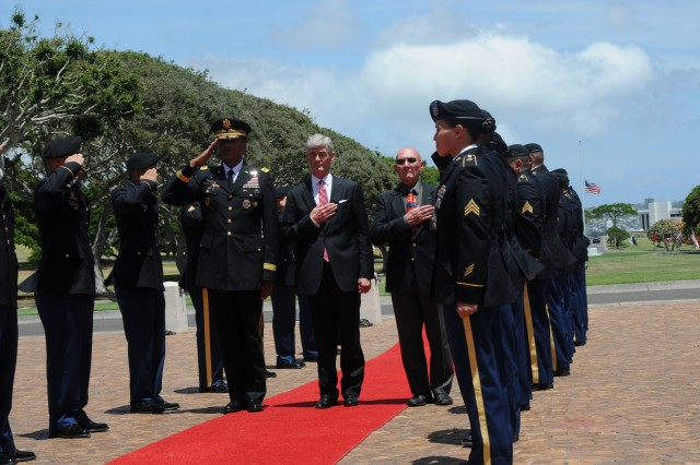 Gen. Vincent K. Brooks, U.S. Army, Pacific commanding general (left), Secretary of the Army John McHugh (center) and Gene Castagnetti, director of the cemetery, salute during the beginning of a wreath-laying ceremony honoring the late Senator Daniel K. Inouye at the National Memorial Cemetery of the Pacific on Honolulu, Hawaii.