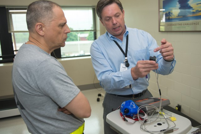 Maj. Gen. Dean G. Sienko, commander, U.S. Army Public Health Command, listens as Todd Hoover, Army Wellness Center Program director, explains how metabolic testing equipment measures the amount of oxygen an individual uses to sustain normal functions.