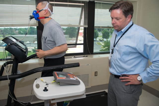 Maj. Gen. Dean G. Sienko, commander, U.S. Army Public Health Command, works out on a treadmill to determine his exercise metabolic rate and assess his cardio-respiratory fitness level as Todd Hoover, Army Wellness Center Program director, monitors his progress.