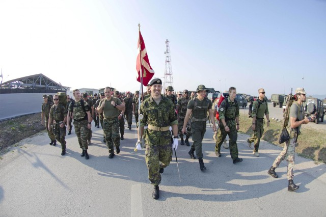 Danish Armed Forces lead the way with the Danish flag at the beginning of the Danish Contingency March July 20 at Camp Novo Selo. More than 750 soldiers and civilians participated in the march. (U.S. Army photo by Sgt. Samantha Parks, 4th Public Affairs Detachment)