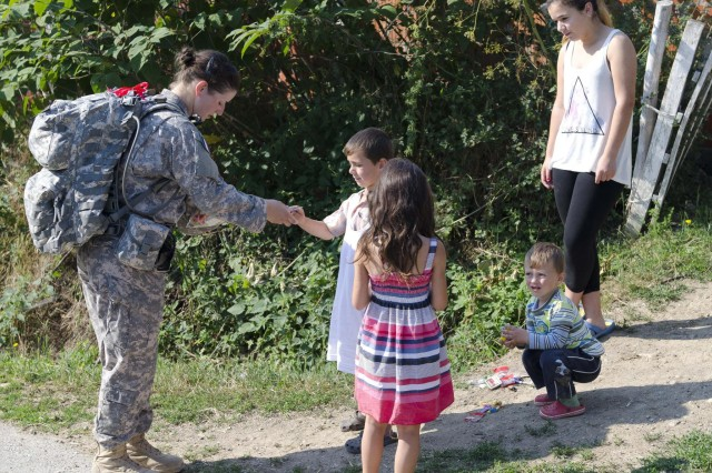 U.S. Army Spc. Shelby Hartman, a soldier with Task Force Aviation, stops to hand out candy to local children during the Danish Contingency March July 20 at Camp Novo Selo. The DANCON route took participants through farm land and nearby villages. (U.S. Army photo by Sgt. Samantha Parks, 4th Public Affairs Detachment)