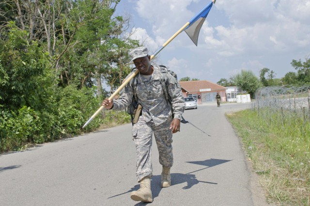 U.S. Army Sgt. Julian Moore, a soldier with Multinational Battle Group-East, carries his unit guidon during the Danish Contingency March at Camp Novo Selo July 20. More than 750 participants completed the 25km march in under six hours. (U.S. Army photo by Sgt. Samantha Parks, 4th Public Affairs Detachment)
