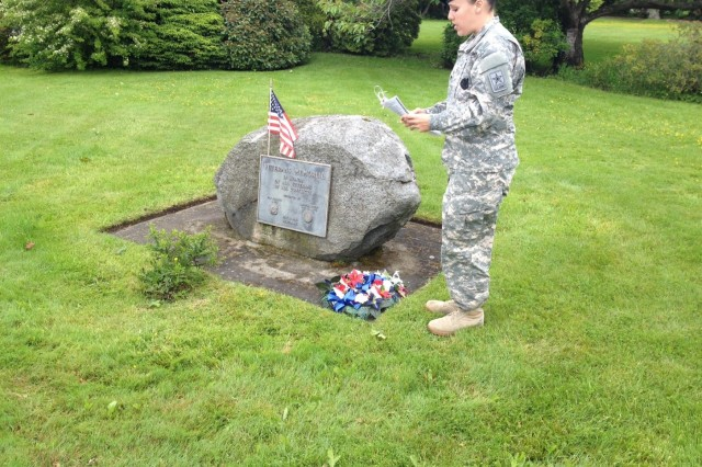 Staff Sgt. Tristan Ryan, a recruiter at Port Angeles Recruiting Station, Wash., lays flowers on a memorial in Sequim Wash., during a Memorial Day ceremony. She stood in for the junior vice commander of VFW Post 4760. (Photo by Rischelle Heaton, president, VFW Post 4760 Woman's Auxiliary, Sequim, Wash.)