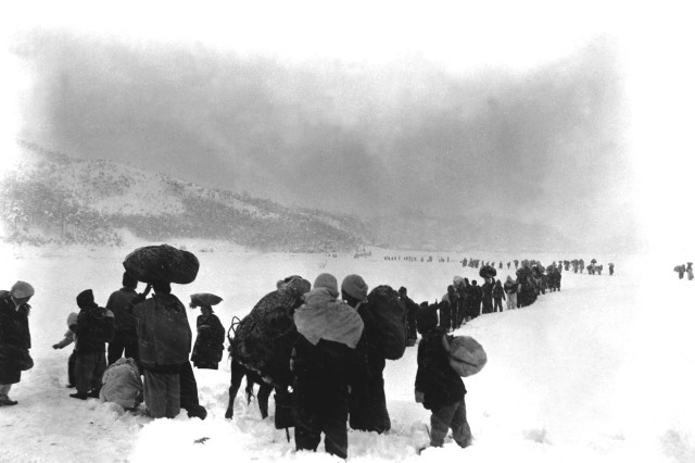 In a Jan. 8, 1951 photo, a long column of Korean refugees plods south through the snow outside Kangnung in Kangwon Province.