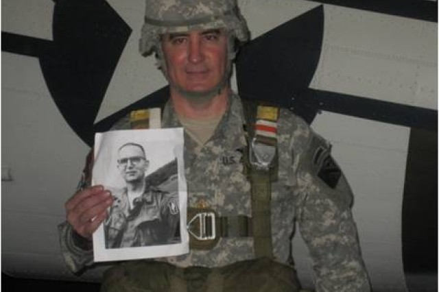 Chaplain (Maj.) Sean Wead holds a photograph of Chaplain (Maj.) Charles J. Watters, who was posthumously awarded the Medal of Honor for his heroism in Vietnam.