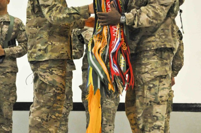 Col. D.A. Sims (left), commander of Combined Task Force Dragoon (2nd Cavalry Regiment), and Command Sgt. Maj. Wilbert E. Engram, senior enlisted advisor for the task force, uncase the task force's colors during a transfer-of-authority ceremony, July 25, 2013, at Kandahar Airfield, Afghanistan. The ceremony formally marked CTF Dragoon's assumption of authority for operations in Regional Command-South in support of Operation Enduring Freedom.