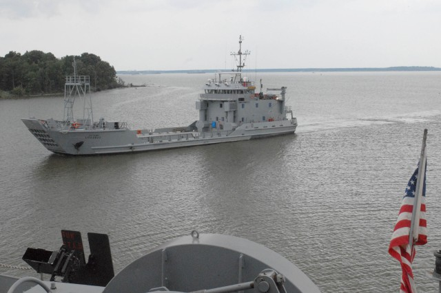 An Army vessel passes by the docked Maj. Gen. Robert Smalls, a Logistics Support Vessel operated by the 805th Transportation Detachment of Tacoma, Wash., at Fort Eutis, Va.