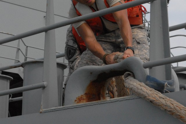 A Soldier from the 805th Transportation Detachment prepares to dock the Maj. Gen. Robert Smalls, a Logistics Support Vessel, July 24, 2013, at Fort Eutis, Va.