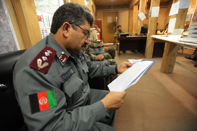 Afghan Uniform Police Col. Abdullah Safi, operations officer, Organizational Coordination Center-Provincial, studies a document during a meeting at the OCC-P headquarters, Asadabad, July 16, 2013. The OCC-P brings various branches of the Afghan National Security Forces together in order to plan and coordinate an efficient response to any security issue that may arise in the province. (U.S. Army National Guard photo by Staff Sgt. Jerry Saslav, 129th Mobile Public Affairs Detachment/RELEASED)