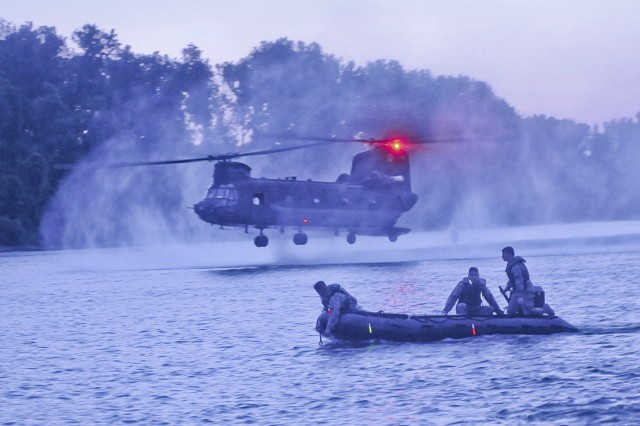 A U.S. Army CH-47 Chinook helicopter assigned to the 7th Aviation Battalion, 158th Aviation Regiment, drops buoys as divers assigned to the 511th Engineer Dive Detachment, 30th Engineer Battalion, 20th Engineer Brigade, from Fort Bragg, N.C., look on during Operation River Assault at Fort Chaffee, Ark., July 24, 2013.