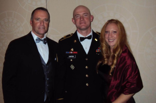 Sgt. Ty M. Carter, a section leader with A Troop, 8th Battalion, 1st Calvary Regiment, 2nd Stryker Brigade Combat Team, 2nd Infantry Division, stands between his father, Mark A. Carter, and his girlfriend, Shannon E. Matson, before being awarded the USO's prestigious George Van Cleave Military Leadership Award at the organization's 50th Annual Gala in New York, Dec. 7, 2011.