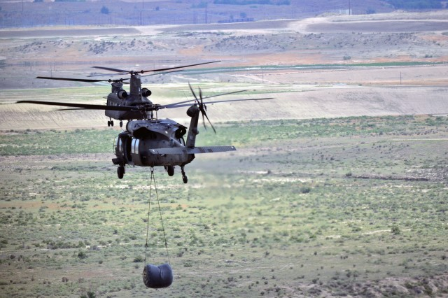 A CH-47 Chinook and UH-60 Black Hawk from 2nd General Support Aviation Battalion, 4th Aviation Regiment, 4th Combat Aviation Brigade, 4th Infantry Division, fly back to Butts Army Airfield after sling-load training, during 4th CAB's first field training exercise, on Fort Carson, Colo., July 25, 2013.