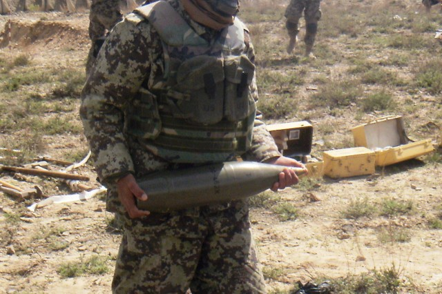An Afghan National Army D-30 Howitzer Cannoneer from 4th Kandak, 2nd Brigade, 203rd Corps, brings a round to the ANA section chief to verify the correct projectile, April 18, 2013, near Orgun, Afghanistan.