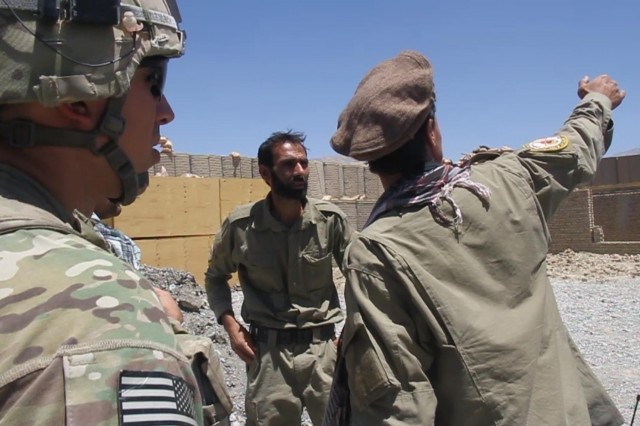 An Afghan Local Police member (right) briefs Afghan Local Police officer Hamad (center), the assistant commander for the local checkpoint, on the security patrol the policemen conducted, July 18, 2013, in the Muhammad Aghah district of Logar Province, Afghanistan, in order to deter enemy activity in the area. First Lt. Alexander Ulrich (left), a Medina, Ohio, native, and a platoon leader with Troop B, 6th Squadron, 8th Cavalry Regiment, 4th Infantry Brigade Combat Team, 3rd Infantry Division, was there to advise and assist as the Afghan Local Police plan and lead security patrols in the area.