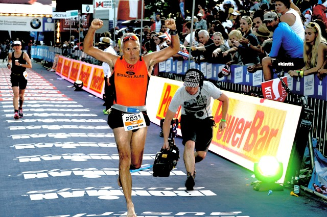 A cameraman shoots video of Tom Romano's shoeless feet as the barefoot runner crosses the Ironman triathlon finish line in Klagenfurt, Austria, June 30.
