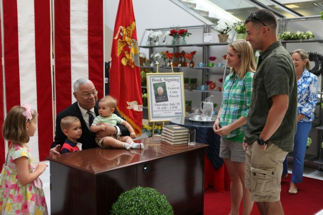 Colin Powell (center) poses for a photograph with (from the left) 5-year-old Maddie, 3-year-old Oscar and 8-month-old Henry during a book signing at the MCX on Joint Base Myer-Henderson Hall June 25, 2013. Mom, Megan Malone (second right) and dad Army Maj. Joe Malone watch.