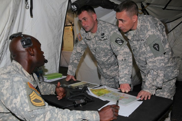 Sgt. 1st Class Brian Piggee, Warrant Officer Shane Bradburn and Chief Warrant Officer 2 Jim Balderas, Training students assigned to 2-13th Aviation Regiment, discuss the upcoming scenario while reviewing the Area of Operations overlay map, during the first enlisted and warrant officer combined Culminating Training Exercise, July 18, 2013, at Fort Huachuca, Ariz.