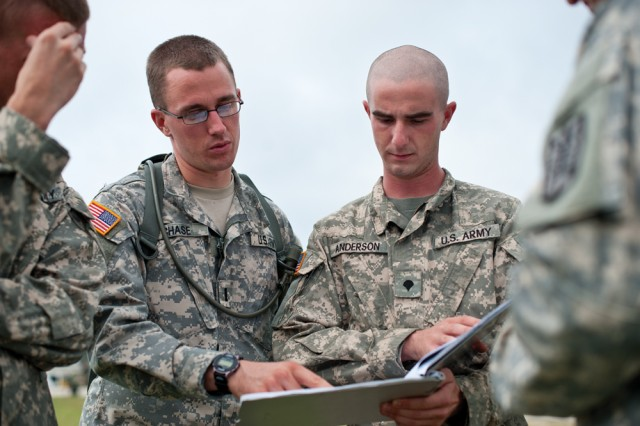 1st Lt. Matthew Chase, a mission briefing officer, and Spc. David Anderson, mission coordinator, huddle to review weather reports prior to launching the MQ-5B Hunter unmanned aerial system.