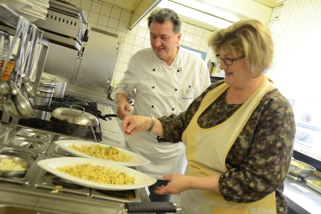 """Andreas Hoessl and his wife, Andrea, put the finishing touches on two plates of kaesespaetzle (a German version of macaroni and cheese) at their restaurant """"Zum Stich'n"""" in Grafenwoehr."""