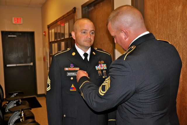 Sgt. 1st Class Mark Yoho, a trainer/mentor with the 1-410th Field Artillery, 4th Cavalry Brigade, First Army Division East, inspects Sgt. 1st Class Philip Whitesell's uniform, before he goes into the Audie Murphy Board at the 157th Infantry Brigade on Camp Atterbury, Ind., Jul 18. (U.S. Army photo By Capt. Olivia Cobiskey, 205th Infantry Brigade Public Affairs)