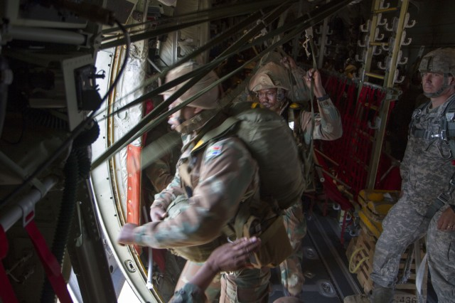 South African Soldiers shuffle to jump out of the C-130 aircraft for a practice jump over the Mimosa Flat Drop Zone, South Africa, July 23. U.S. Army Capt. Craig D. Arnold, commander of Charlie Company, 1st Battalion, 325th Airborne Infantry Regiment from Fort Bragg, N.C., was a jumpmaster for the practice jump, in preparation for an exercise that South African and U.S. Soldiers will conduct jointly during Shared Accord 13. Shared Accord is a biennial training exercise which promotes regional relationships, increases capacity, trains U.S. and South African forces, and furthers cross-training and interoperability. The jump will also earn each Soldier a pair of foreign wings for either jumping in a foreign country or jumping with a foreign country's jumpmasters.