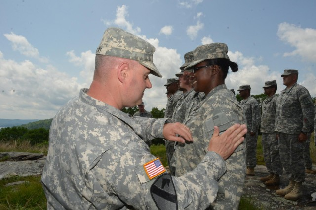 Camp Smith Training Site Command Sgt. Major Thomas Seifert replaces the old patch on a soldiers arm with the new patch of the Training Center Garrison Command during a colors uncasing and re-patching ceremony held for members of the unit on June 3. Camp Smith Post Commander Lt. Col. Robert  Epp and Seifert re-patched the soldiers assigned to Camp Smith  with their new unit patch after the uncasing a new flag for the garrison command. (Photo by Lt. Mark Getman)
