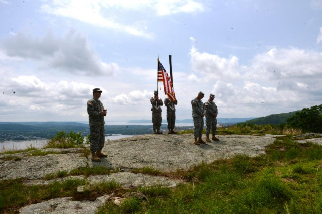 The new colors of Camp Smith Training Site wait to be  unfurled on the highest point of ground on the post, overlooking the Hudson River, during a special unit colors uncasing and re-patching ceremony on June 3rd 2013 as Chaplain (Lt.) Mark Getman (left), delivers the invocation opening the event. Camp Smith Post Commander Lt. Col. Robert Epp and Camp Smith Command Sgt. Major Thomas Seifert re-patched the soldiers assigned to CSTS with their new unit patch after the unit colors uncasing.