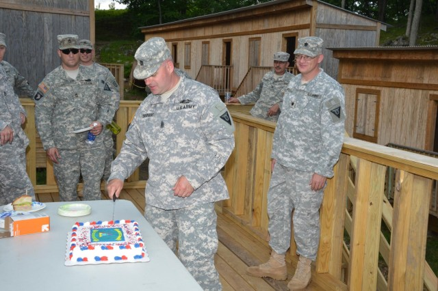 "Camp Smith Training Site Command Sgt. Major Thomas Siefert cuts a cake commemorating the ""re-patching"" of soldiers assigned to the site on June 3. The more than 100-year old training facility now has a new flag and patch as part of the National Guard's Training Center Command."