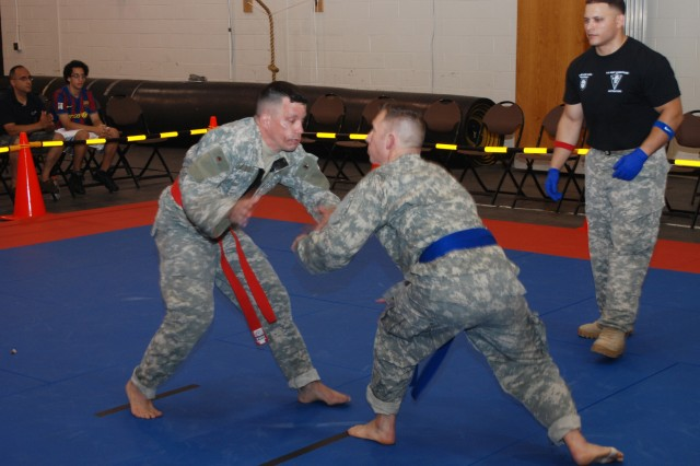 CAMP SMITH, N.Y. - Staff Sgt. Sean Lockhart, 1st Battalion, 106th Regional Training Institute (left) begins to grapple with Staff Sgt. Theodore Albright, 204th Engineer Battalion (middle), during the New York Army National Guard's first annual Combatives Tournament, held here July 27. Staff Sgt. Abismael Gonzalez, tournament non-commissioned officer in charge (right), referees the match. Combatives is a combination of Judo, Jujitsu and other techniques which enables American troops to prevail in hand-to-hand combat. The 1st Battalion, 106th Regional Training Institute (RTI), organized and held the tournament, and winners may have an opportunity to represent New York State in the All Army National Guard Combatives Tournament to be held at Ft. Benning, Ga. in 2014.