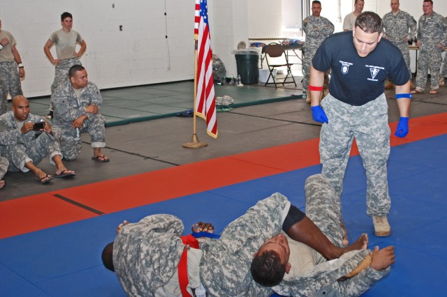 CAMP SMITH, N.Y. -- Sgt. Adama Ilboudi, 719th Transportation Company (left) grapples with Sgt. Alexis Bruno, 1st Battalion, 69th Infantry (middle), during the New York Army National Guard's first annual Combatives Tournament, held here July 27. Staff Sgt. Abismael Gonzalez, tournament non-commissioned officer in charge (right), referees the match. Combatives is a combination of Judo, Jujitsu and other techniques which enables American troops to prevail in hand-to-hand combat. The 1st Battalion, 106th Regional Training Institute (RTI), organized and held the tournament, and winners may have an opportunity to represent New York State in the All Army National Guard Combatives Tournament to be held at Ft. Benning, Ga. in 2014.  Ilboudi, who took first place in the heavy weight category is holding Bruno in a  lower arm bar and head lock.