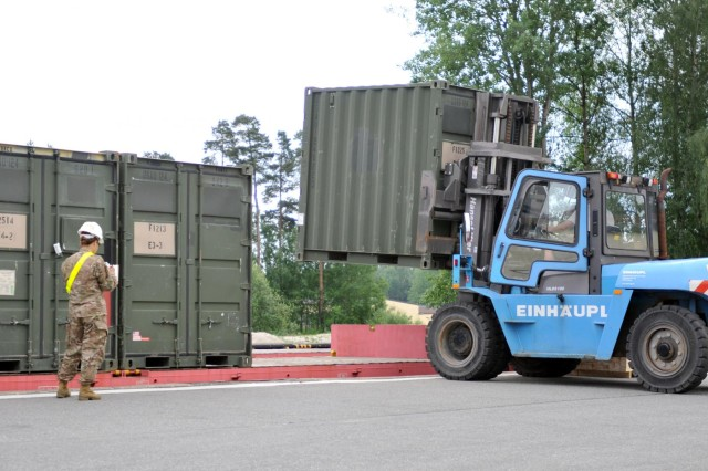 Sgt. Sheryl Willson, a transportation non-commissioned officer in charge with the 2nd Cavalry Regiment, and a native of Maui, Hawaii, watches as a TRICON type container is loaded onto a railcar, June 21, 2013. More than 200 containers were loaded onto railcars in preparation for the containers' trip to Mihail Kogalniceanu, Romania, where, with the coordination of the 21st Theater Sustainment Command, the 627th Movement Control Team, 16th Sustainment Brigade and the Air Force's 627th Contingency Response Group, they will be flown to their final destination in Afghanistan to support 2nd Cavalry Regiment's mission there.