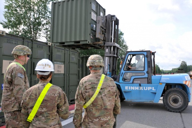 Soldiers with the 2nd Cavalry Regiment watch as a TRICON type container is loaded onto a railcar here, June 21, 2013. More than 200 containers were loaded onto railcars in preparation for the containers' trip to Mihail Kogalniceanu, Romania, where, with the coordination of the 21st Theater Sustainment Command, the 627th Movement Control Team, 16th Sustainment Brigade and the Air Force's 627th Contingency Response Group, they will be flown to their final destination in Afghanistan to support the 2nd Cavalry Regiment's mission there.