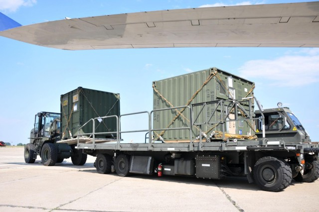 An Airman with the 627th Movement Control Team uses a forklift truck to load a TRICON container onto a cargo lifter prior to it being loaded onto a Boeing 747 cargo jet in Mihail Kogalniceanu, Romania, July 14, 2013. The 21st Theater Sustainment Command, along with the 627th Movement Control Team, 16th Sustainment Brigade and the Air Force's 435th Contingency Response Group moved more than 200 TRICON containers into Afghanistan for the 2nd Cavalry Regiment, taking nine round trips by two B-747s.