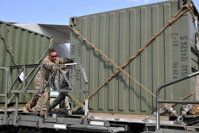 Sgt. Robert Epley, a truck driver with the 2nd Cavalry Regiment and a native of Morganton, N.C., helps push a TRICON container onto a cargo lifter, prior to it being loaded onto a Boeing 747 cargo jet in Mihail Kogalniceanu, Romania, July 14, 2013. The 21st Theater Sustainment Command, along with the 627th Movement Control Team, 16th Sustainment Brigade and the Air Force's 435th Contingency Response Group moved more than 200 TRICON containers into Afghanistan for the 2nd Cavalry Regiment, taking nine round trips by two B-747s.
