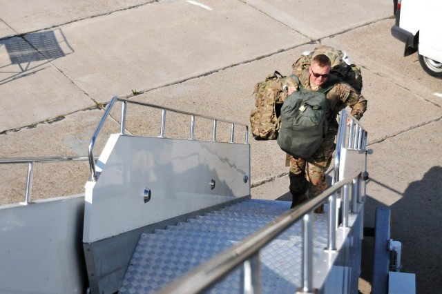 First Lt. Walden Wagner, with the 2nd Calvary Regiment, and a native of Spokane, Wash., boards a Boeing 747 cargo jet at the airport in Mihail Kogalniceanu, Romania, prior to its departure for Afghanistan, July 14, 2013. The aircraft was at the airport to transport its share of more than 200 TRICON containers belonging to the 2nd Calvary Regiment to support their mission in Afghanistan.