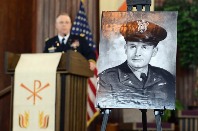 A photo of Medal of Honor recipient Chaplain (Capt.) Emil J. Kapaun is on display at a memorial service honoring the Korea War priest who died a prisoner of war in May 1951. Maj. Gen. Donald Rutherford, U.S. Army chief of chaplains, is speaking in the background, at the event at Joint Base Myer-Henderson Hall, Va., July 26, 2013.