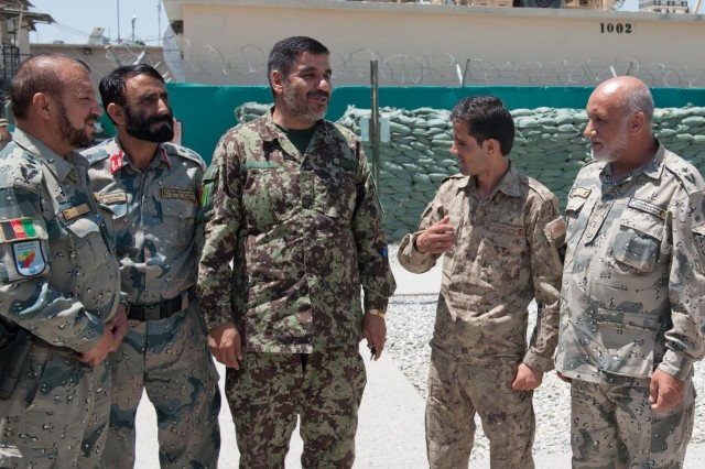 Intelligence officers from the Afghan Border Police, Afghan National Army and Afghan National Civil Order Police share a light moment after an intelligence meeting at Forward Operating Base Fenty, Nangarhar province, Afghanistan, July 8, 2013. This was the third time U.S. Army intelligence personnel met face-to-face with their Afghan counterparts to trade notes on securing the Nuristan-Kunar-Nangarhar region, and the first time the ANA was represented as well. (U.S. Army photo by Sgt. Margaret Taylor, 129th Mobile Public Affairs Detachment)