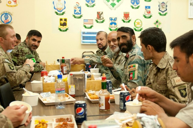 Intelligence officers from the Afghan Border Police, Afghan National Army and Afghan National Civil Order Police share a light moment with their U.S. Army counterparts over lunch following an intelligence meeting at Forward Operating Base Fenty, Nangarhar province, Afghanistan, July 8, 2013. This was the third time U.S. Army intelligence personnel met face-to-face with their Afghan counterparts to trade notes on securing the Nuristan-Kunar-Nangarhar region, and the first time the ANA was represented as well. (U.S. Army photo by Sgt. Margaret Taylor, 129th Mobile Public Affairs Detachment)