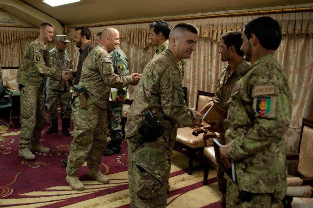 U.S. Army soldiers from 1st Brigade Combat Team, 101st Airborne Division, and their colleagues from 4th BCT, 10th Mountain Div., shake hands with their counterparts from the Afghan Border Police and Afghan National Civil Order Police following an intelligence meeting at Forward Operating Base Fenty, Nangarhar province, Afghanistan, July 22, 2013. During the meeting, the outgoing American intelligence officer/S2 from the 101st introduced the Afghans to his replacement from 10th Mtn. The briefing covered security concerns for Zone 1, which is comprised of the Nangarhar, Nuristan and Kunar provinces in eastern Afghanistan. (U.S. Army photo by Sgt. Margaret Taylor, 129th Mobile Public Affairs Detachment)
