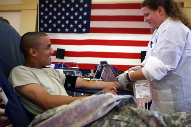Pfc. Hector Ruiz, A Battery, 2nd Battalion, 5th Field Artillery, talks with Sylvia Vincent, collection tech, as he donates blood July 30 at Rinehart Fitness Center. The Tulsa American Red Cross is holding a blood drive this week as part of the Operation Live Well Health Expo. Service members, DA civilians and community members are welcome to donate today from 1-5 p.m. at Rinehart. Red Cross officials hope to collect more than 300 units here.