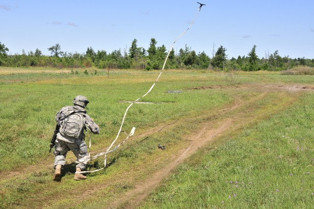 A Soldier assigned to 630th Route Clearance Company, 7th Engineer Battalion, throws a grappling hook tied to engineer tape to clear a lane of all trip wires during a combined-arms platoon live-fire exercise July 25. Live-fire exercises give Soldiers a chance to train how they fight.